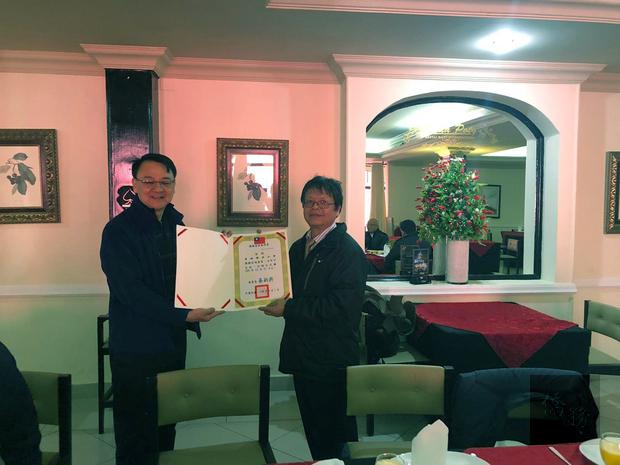 周鄰(左)代表僑委會頒發僑務榮譽職人員聘書給貝多芳中華會館理事長曾錦輝僑務促進委員。