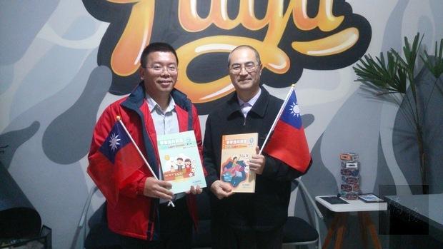 詹前校(左)此次訪視柯太太中文學校,應柯俊同(右)要求,致贈《學華語向前走》教材與手搖小國旗。