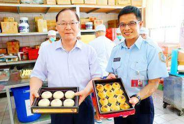 "Changhua Prison Warden Huang Kun-chien, left, and another official on Sunday hold gift boxes of ""iron-bar mooncakes"" and pastries for the Mid-Autumn Festival made by inmates working in the Changhua County prison's bakery."