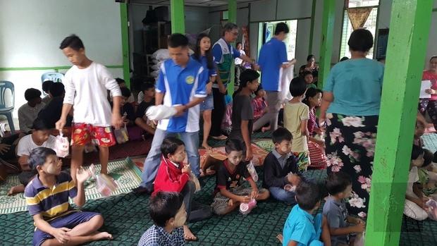 緬甸臺灣商貿會會員分發點心給院童。