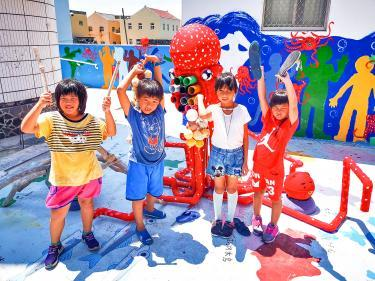 Students hold up pieces of marine debris in front of a musical octopus installation, which they built from trash they gathered on beaches, on the roof of Niaoyu Elementary School in Penghu County's Baisha Township in an undated photograph./Photo cour
