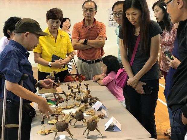 李永謨展現樹皮編塑的各式昆蟲環保手工藝。