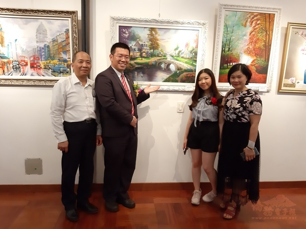 林志孟(左1)、詹前校(左2)共同欣賞巴西僑界青年的油畫作品。