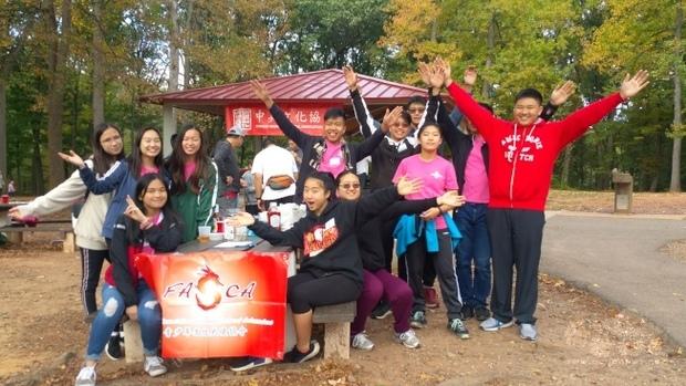 中美文化協會重陽秋遊, 12名FASCA 青少年志工訓練有素地綁條幅、端菜餚,幫助活動順利進行。(世界日報提供)