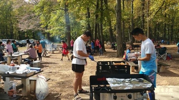 中美文化協會重陽秋遊,義工們現場烤肉陣陣飄香。(世界日報提供)