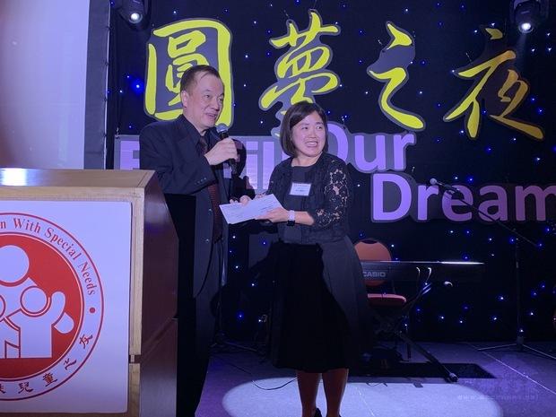 周文(右)代表駐處致贈贊助款予華人特殊兒童之友王彥邦(左)。