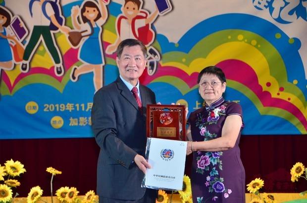 尹新垣(左)頒贈僑委會獎座給服務滿50年屆的陳雲湄教師。