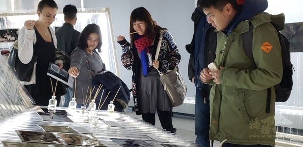 參觀者品香,在不同展示的瓶罐中尋找台灣的味道。(世界日報提供)