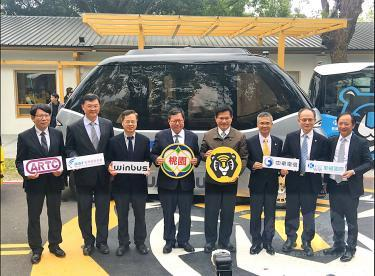 Lin Chia-lung, center right, Cheng Wen-tsan, center left, and other officials, stand in front of an autonomous bus, holding placards with the logos of organizations sponsoring trials of driverless vehicles at a news conference in Taoyuan yesterday. /