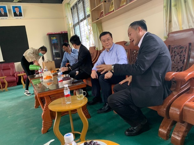 李朝成聽取李明昌介紹聖光中學畢業生到臺灣升學情形。