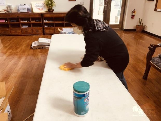 亞特蘭大文教中心主任賴麗瑩用心擦拭放口罩的桌子。
