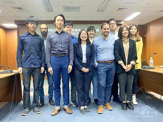 Academia Sinica Institute of Molecular Biology assistant research fellow Hsueh Yen-ping, front row, center, and her research team pose for a group photograph at a news conference in Taipei yesterday./Photo courtesy of CNA