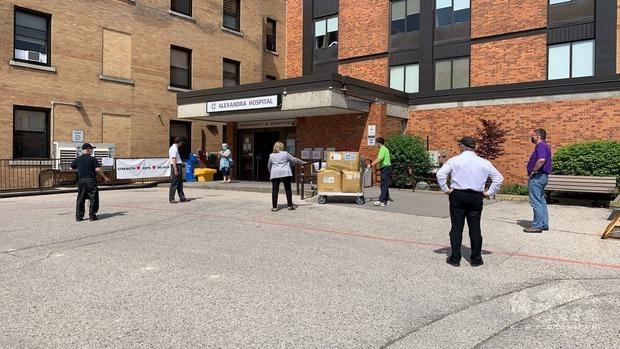 醫院急診室前捐贈防疫物資大家均保持社交距離。