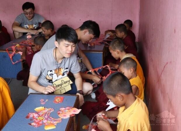 國防醫學院享尼尼泊爾國際志工團團員在佛學院進行元宵節慶課程,教導孩童製作燈籠。