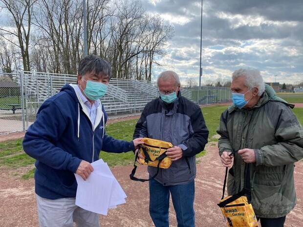 密西根僑界急難救助協會會長張正義(左1)向世界青少棒聯盟總部主席Greg Bzura(中)說明防疫關懷包內容及使用方法。