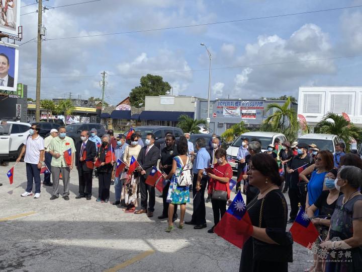 僑胞們手持國旗參加升旗典禮