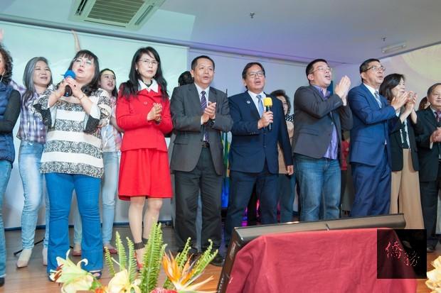 張崇哲處長夫婦(前排左2、左3)等貴賓於民歌演唱會尾聲時上臺大合唱「小草」,祝福中華民國生日快樂。