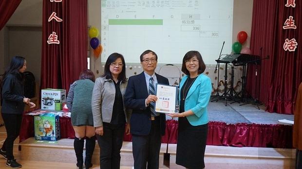 徐詠梅(左)與李叔玲(右)代表僑委會頒發107年國慶有功團體獎狀予王人英(中)。